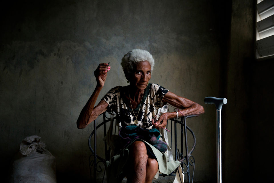 """Leonada Gelato Machena in her one-room apartment. December 2015, Cienfuegos, Cuba.   Leonada shared with me that she loved sitting with friends in the local park, but now, when some of them are already gone she rather stays in the house. She keeps saying that """"getting older"""" does not fit her character at all."""