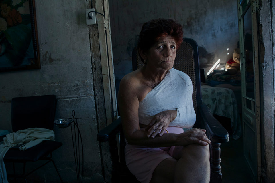 """lama Bural Morachon, in her house. December 2016, Cienfuegos, Cuba. After she slipped and broke her arm and shoulder, she must have assistance for almost everyday action. """"The body betrays you. It is a terrible feeling,"""" she told me. © Oded Wagenstein"""