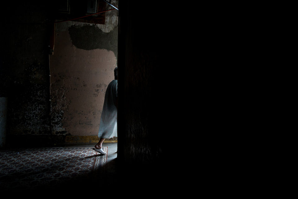 A resident walking down the corridor of the seniors' apartment complex. December 2016, Cienfuegos, Cuba. © Oded Wagenstein
